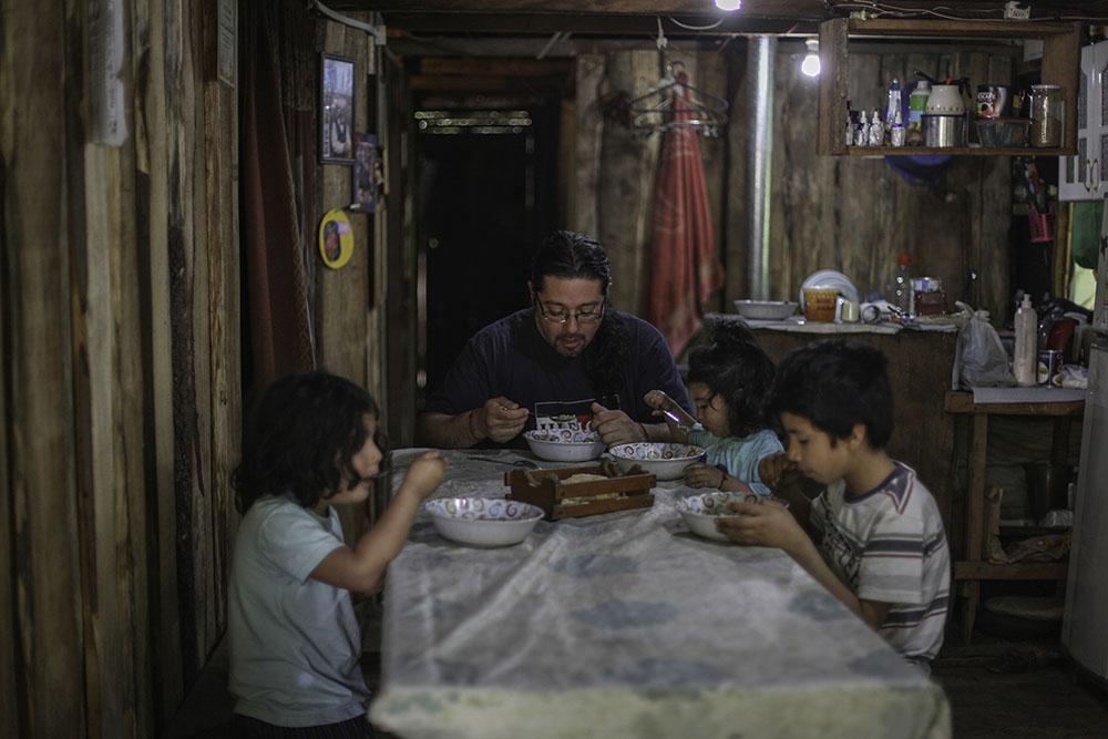 Ruben Collio junto a sus hijos almuerza en su casa en la localidad de Tranguil.©Ruta35r/Cristobal Saavedra