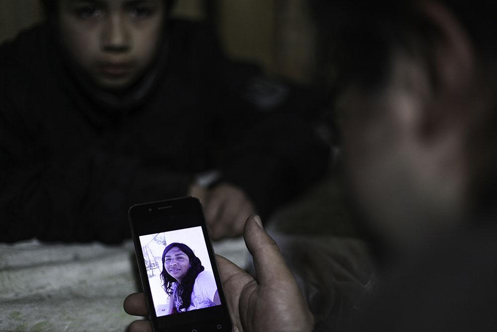 Ruben Collio junto a su hijo miran una fotografia de Macarena en su celular.©Ruta35r/Cristobal Saavedra