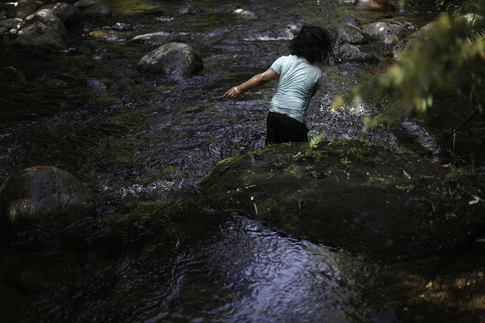 Hijo de Ruben Collio juega en un pequeño rio que pasa bajo su terreno en la localidad de Tranguil.©Ruta35r/Cristobal Saavedra