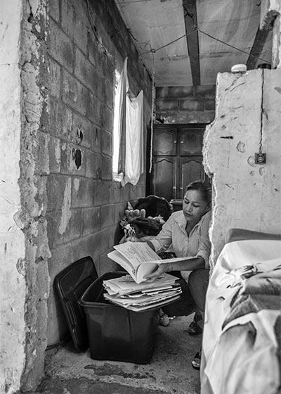 Marcela busca en una caja la libreta de su hijo Cosme, donde solía escribir pensamientos y citas bíblicas.
